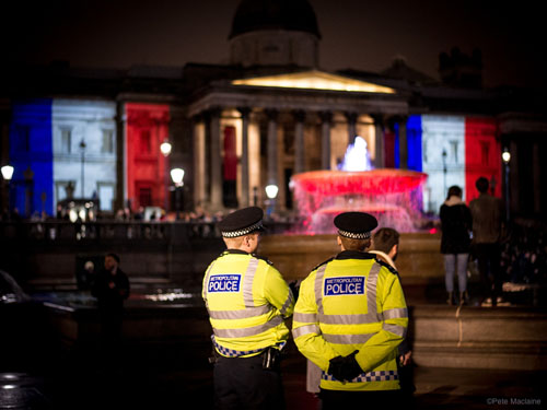 London, UK. 14 November, 2015. Metropolitan Police Officers stand guard as thousands gather in Trafalgar Square for a candlelit vigil in solidarity with the victims of last night's terrorists attacks in Paris.